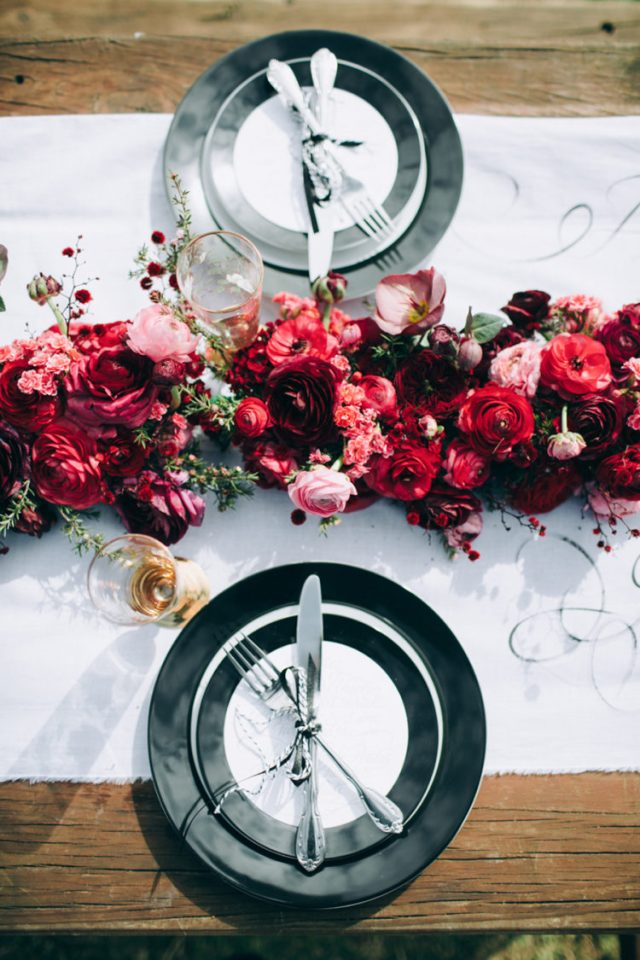 a stylish tablescape done with lush red and pink blooms, a white runner and black and white plates and chargers