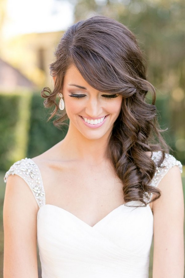a side curl wedding hairstyle with a bang looks luxurious and vintage-inspired