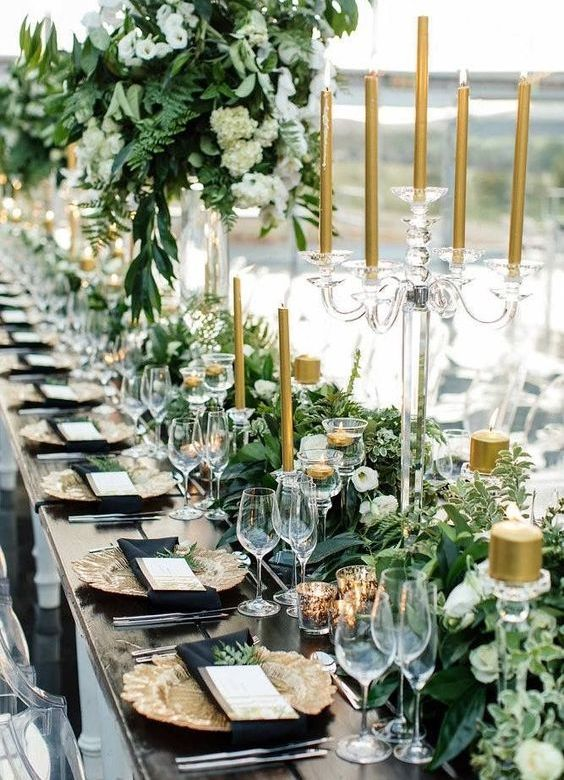 black and gold wedding reception table with lush greenery and gold candles