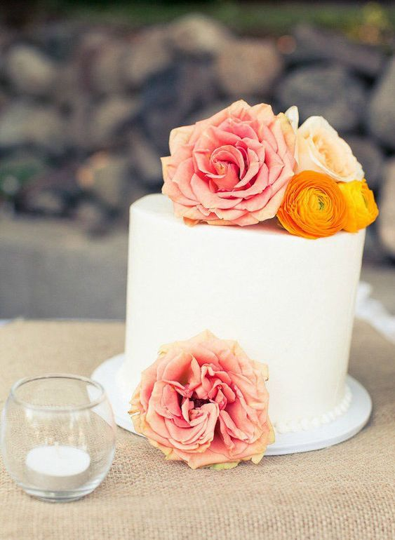 a beautiful buttercream one tier wedding cake topped with orange and pink blooms is a great idea for a bright summer wedding