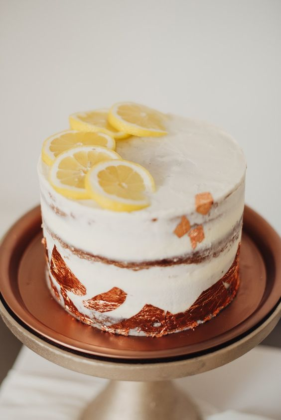 a one tier naked wedding cake decorated with copper leaf and some citrus slices on top looks very modern and bold
