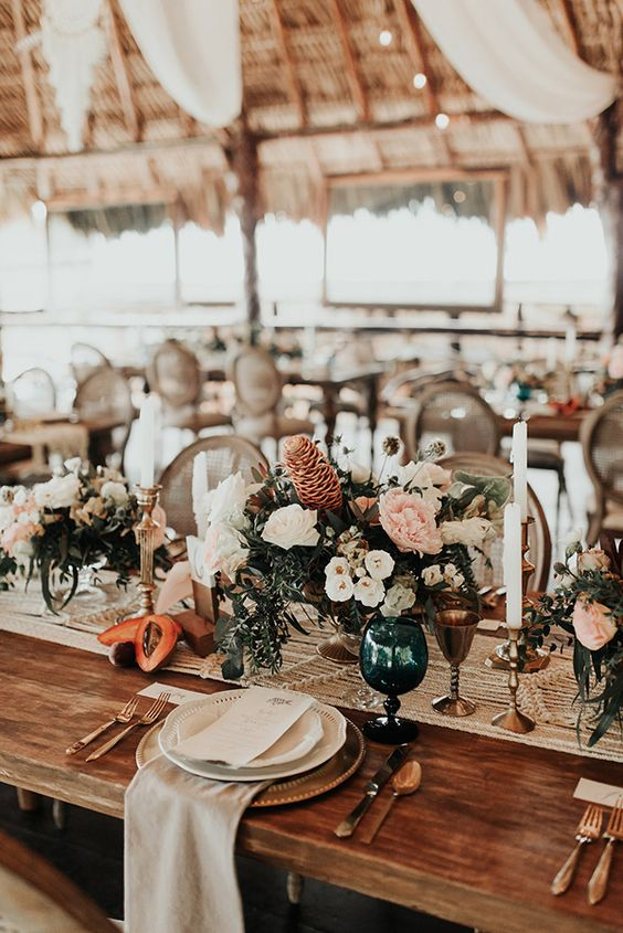 a beach boho wedding tablescape with a macrame table runner, fruits, lush florals, candles and a neutral napkin