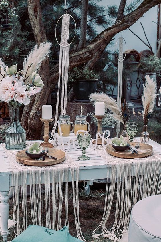 a boho tablescape with a whitewashed table, macrame placemats, colored glasses, candles and florals