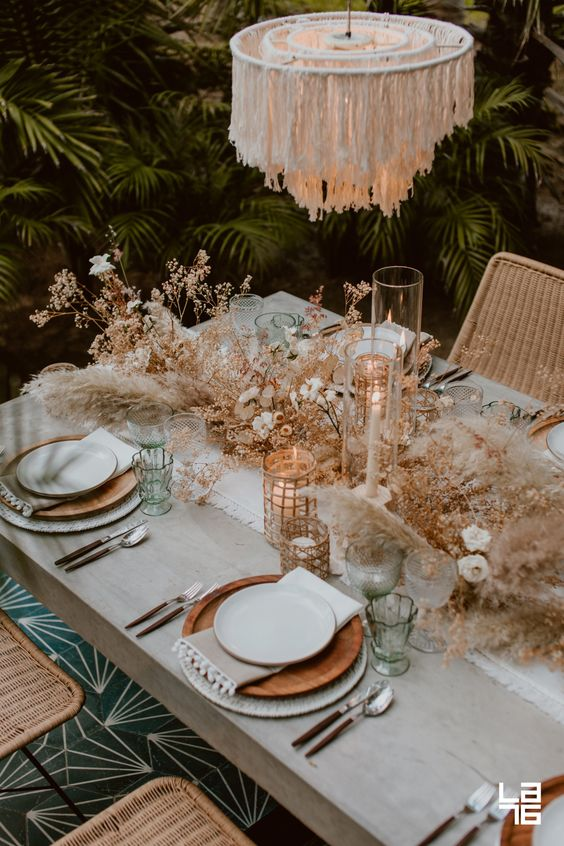 a chic desert boho tablescape with wooden plates, a fringe chandelier, candles, dried herbs and blooms plus pampas grass