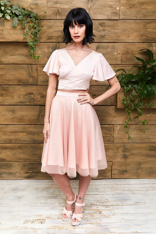 a cool ensemble of a pink silk crop top with bell sleeves and a V-neckline plus a knee pleated skirt and platform shoes