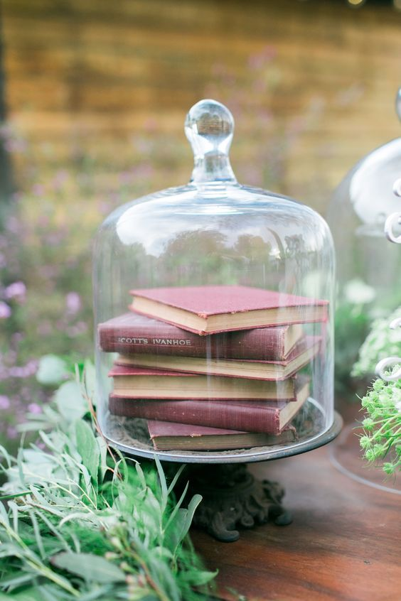 a cloche with book inside is a simple and laconic centerpiece idea, add some greenery around or inside