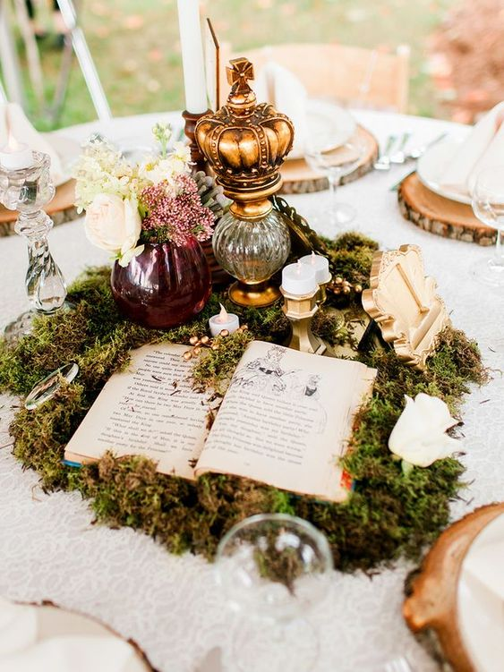 a magical wedding centerpiece composed of moss, an opened book, candles, vases with blooms and a table number