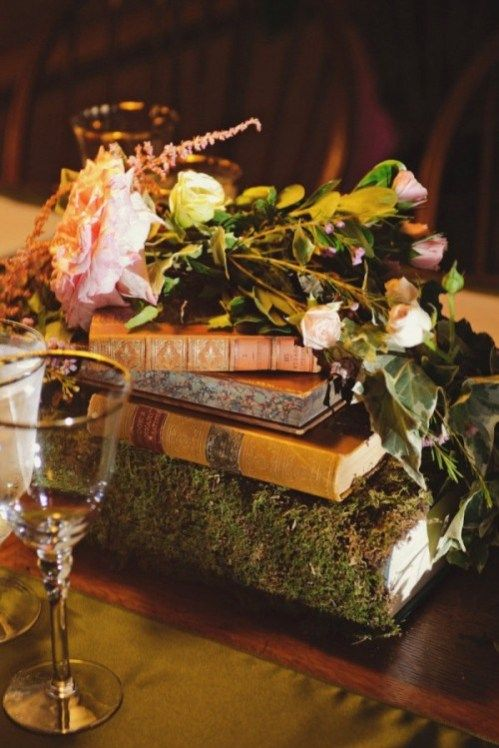 a stack of books, one of them covered with moss and with lots of lush blooms on top