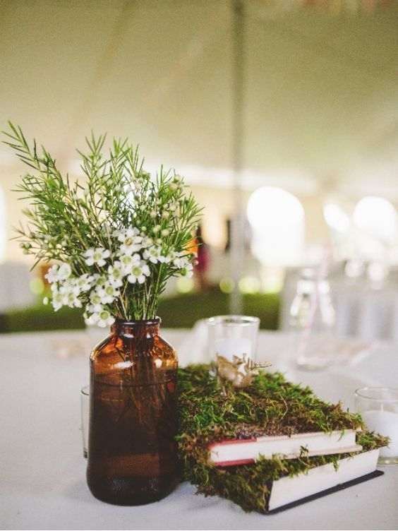 moss covered books, an amber glass vase plus wildflowers and greenery is a simple and rustic idea