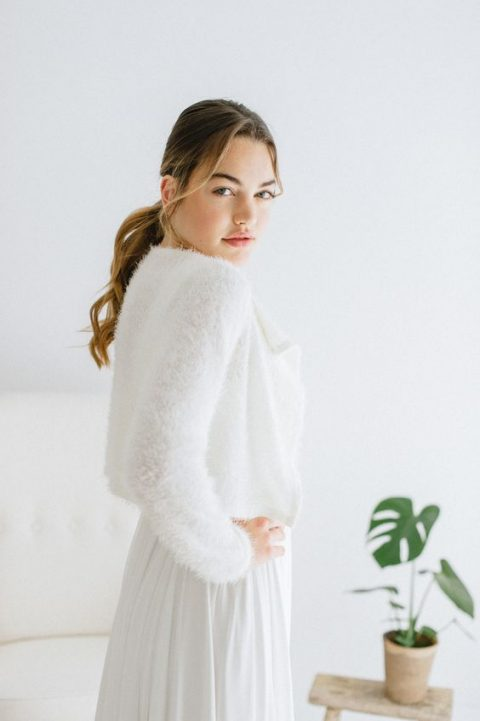 a very cozy white fluffy angora sweater over the wedding dress looks sophisticated