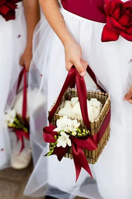 a stick flower girl basket decorated with burgundy ribbons and white blooms