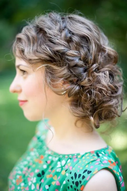 a curly updo with a low bun and a braided halo is a chic hairstyle that will last all day long