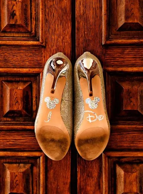 sparkling gold wedding shoes with Micckey Mouse heads and Disney letters on the bottoms