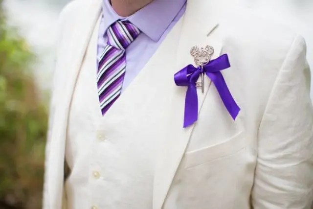 a creamy three-piece suit, a lavender shirt, a striped tie, a Mickey Mouse themed key boutonniere with a bow