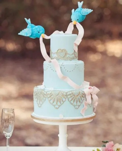 an aqua wedding cake with gold lace and little birdies with a ribbon like in Disney's cartoons