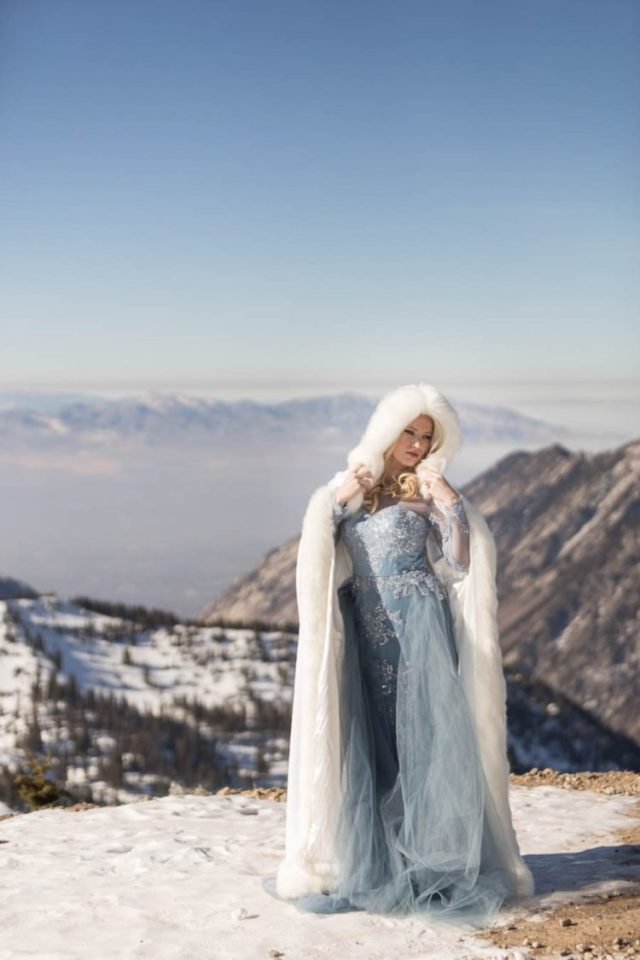 Elsa-inspired bridal look with a blue embellished wedding dress with long sleeves and an illusion neckline plus a faux fur coverup with a hood