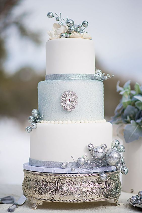 a Frozen themed wedding cake in white and light blue with a touch of glitter pplus rhinestones and embellishments