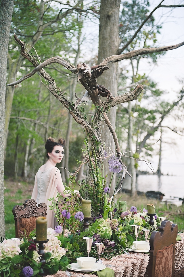 a Maleficent-inspired wedding table setting with lots of greenery, bold blooms, green candles, branches and silver goblets