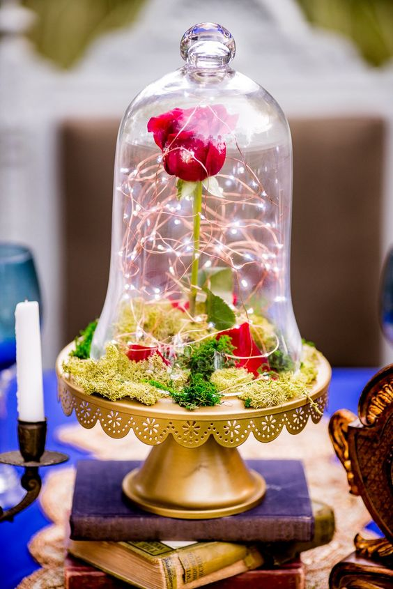 a bold the Beauty and the Beast wedding centerpiece of a gold cloche with moss, a single red rose and LEDs