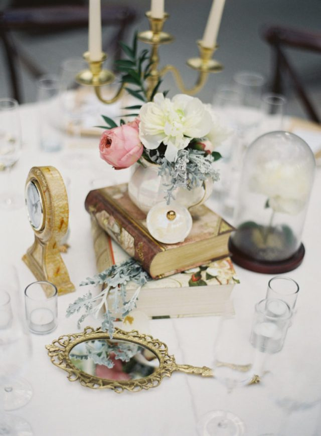 a creative Disney wedding centerpiece with vintage books, a clock, a cloche with a flower, a hand mirror and blooms