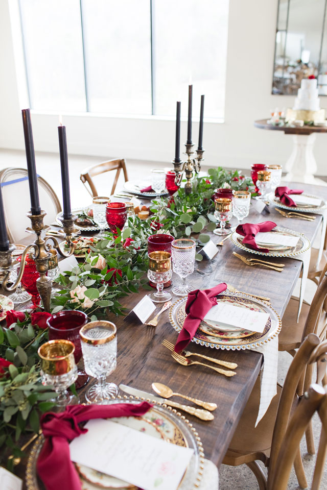 a gorgeous the Beauty and the Beast wedding tablescape with greenery and bright blooms, burgundy napkins, black candles and touches of gold