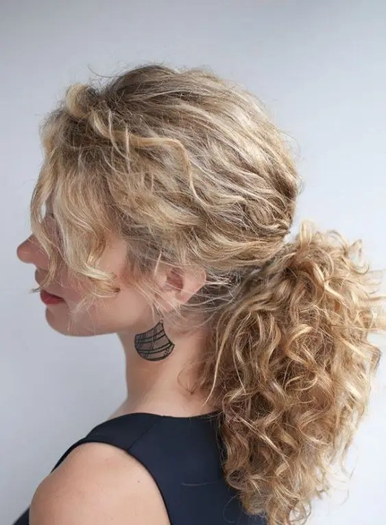 a messy low ponytail with bangs is a chic idea to rock for a modern wedding, it will take you a minute to make