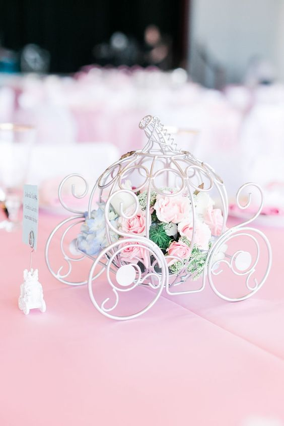 a refined white carriage filled with fresh blooms and greenery is a cute and chic Disney themed wedding centerpiece