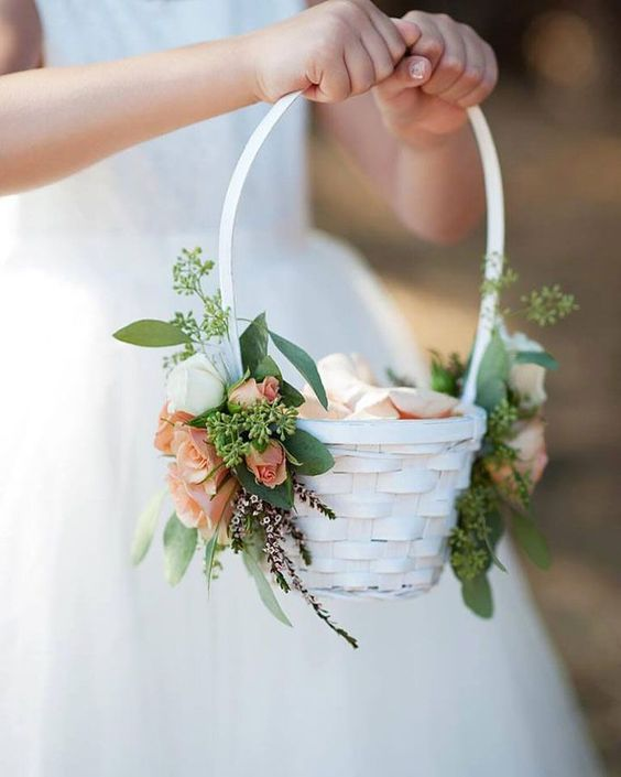 a simple white basket to carry flower petals adorned on each side with spray roses and seeded eucalyptus