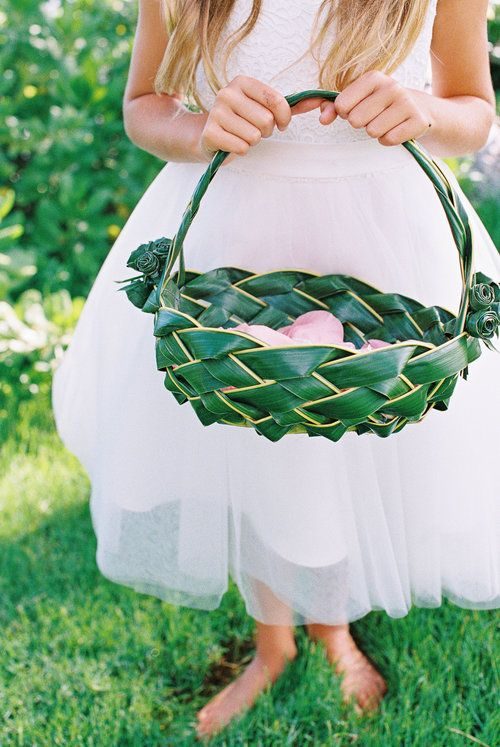 a unique flower girl basket made of a tropical leaf interwoven and decorated with blooms made of it, too