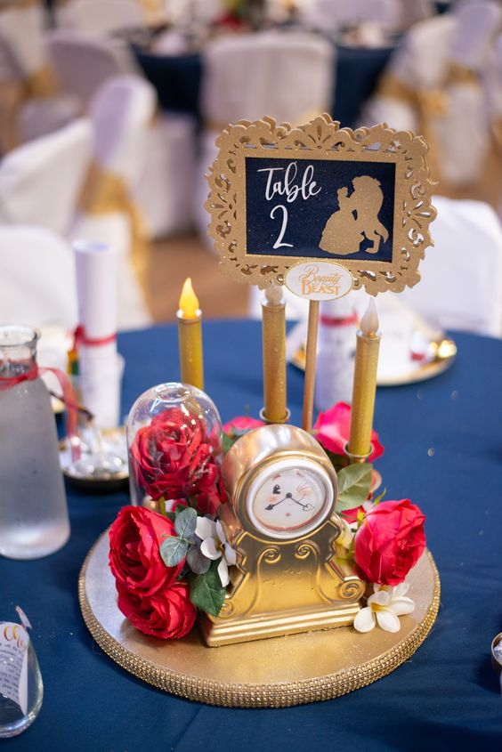 the Beauty and the Beast wedding centerpiece with a clock, red roses and fake candles plus a framed table number