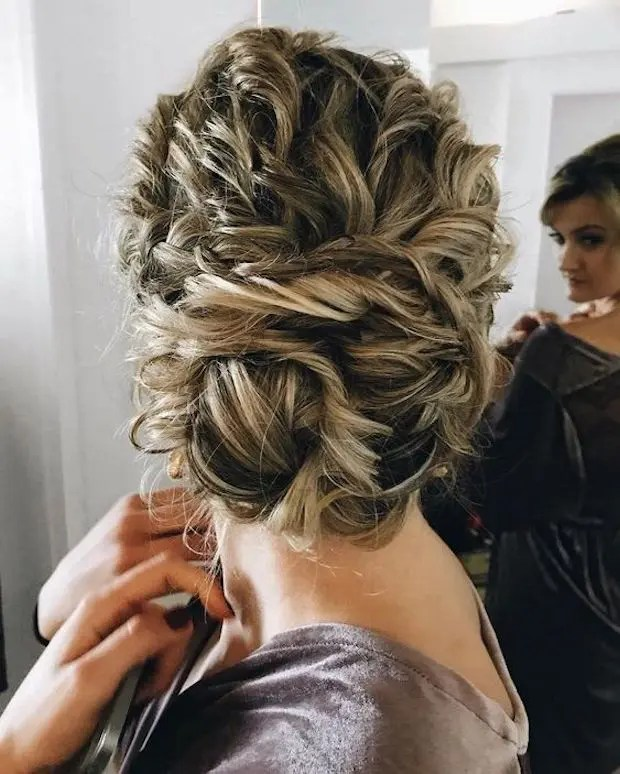 tie up your curly hair into a large twisted low bun, it will look very textural and messy, which is trendy