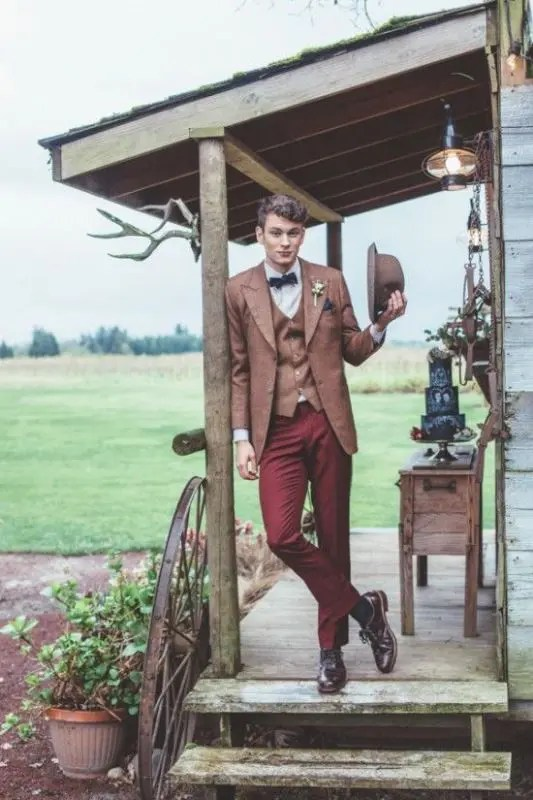a vintage barn groom's look with burgundy pants, a rust blazer and waistcoat, a black bow tie, a rust hat and purple shoes