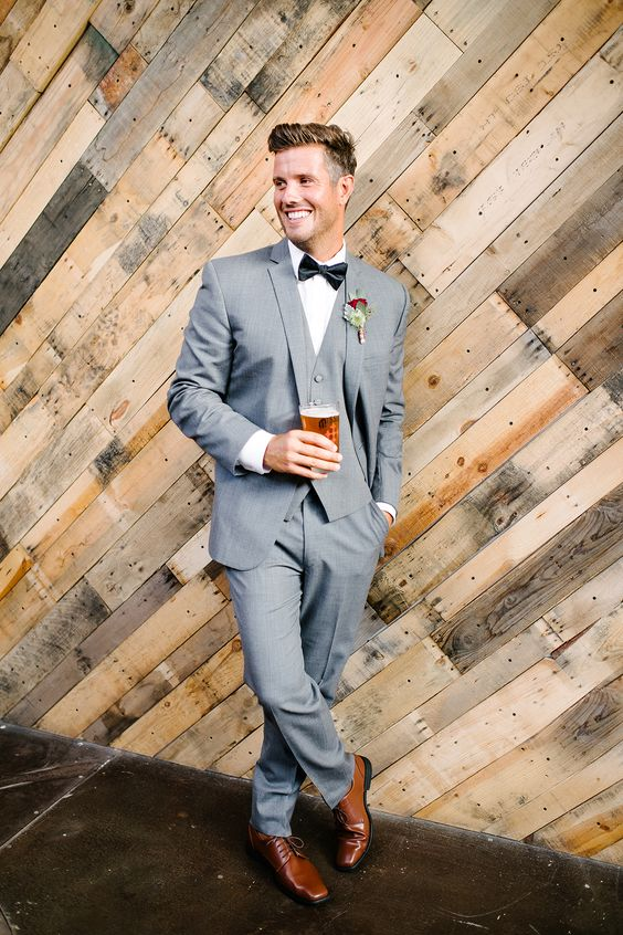 a chic groom's look with a light grey three-piece suit, a black bow tie, a white button down and amber shoes