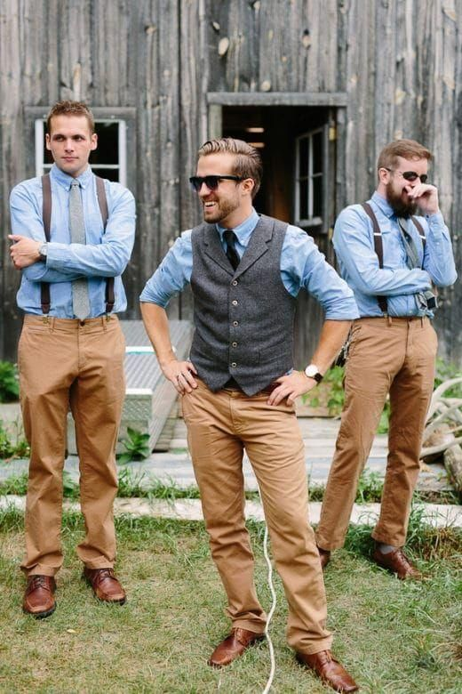 a relaxed barn groom's outfit with a blue button down, a black tie, a grey waistcoat, tan pants and brown shoes
