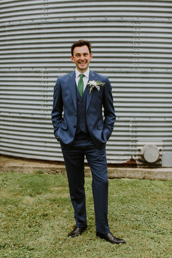 an elegant groom's outfit with a thre-epiece navy suit, an emerald tie, a white button down and black shoes