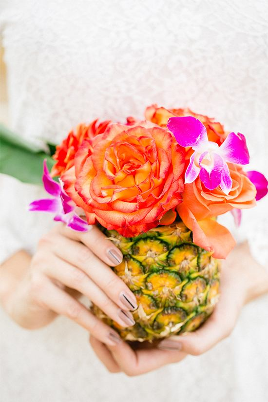 a tropical bridal shower centerpiece of a pineapple with bright florals