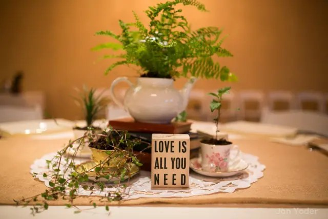 a chic wedding centerpiece of a doily, greenery in vintage teacups, a stack of books and a teapot with ferns growing