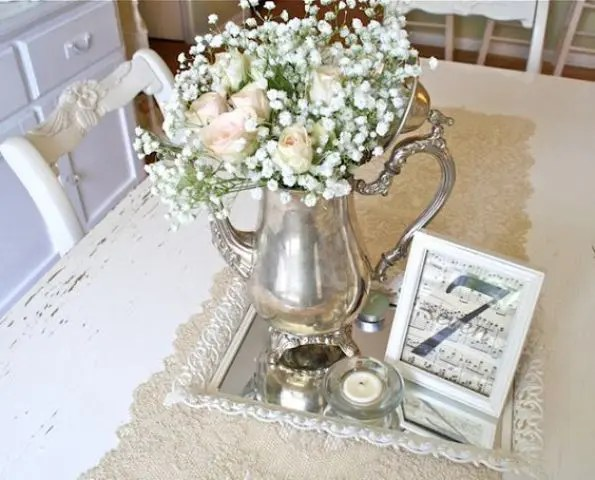 a vintage wedding centerpiece of a silver tray, a silver tea pot with blush roses and baby's breath, candles and notes in a frame