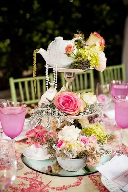 an eye-catchy wedding centerpiece of a mirror, a couple of stands, bright blooms, greenery, pearls and a teapot on top
