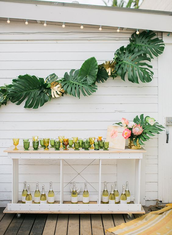 a fun tropical bridal shower drink station with colored glasses, lots of bottles and monstera leaf and king protea arrangements