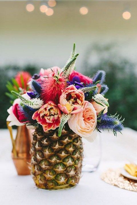 a pineapple centerpiece with a bright floral arrangement and touches of greenery for a tropical bridal shower