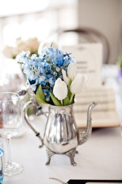 a silver teapot with white tulips and blue hydrangeas for a simple and chic wedding centerpiece