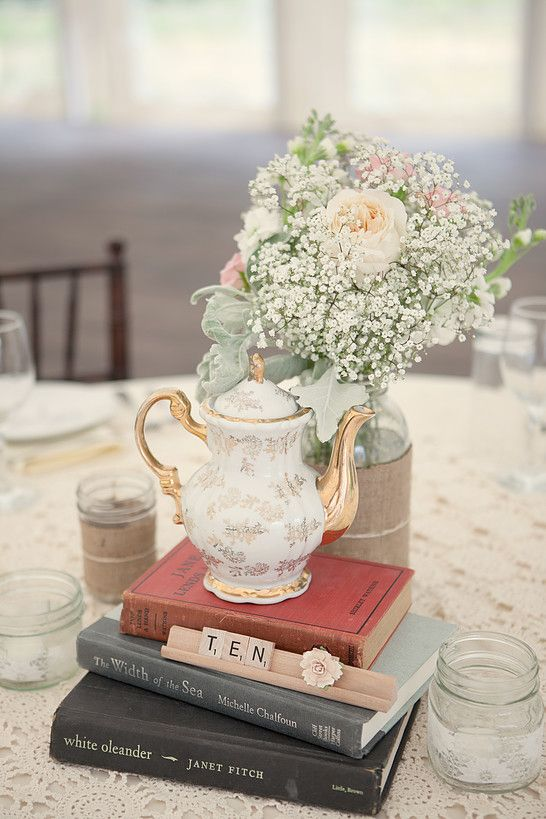 vintage books, a vintage floral teapot, a vase with baby's breath and blush and pink blooms