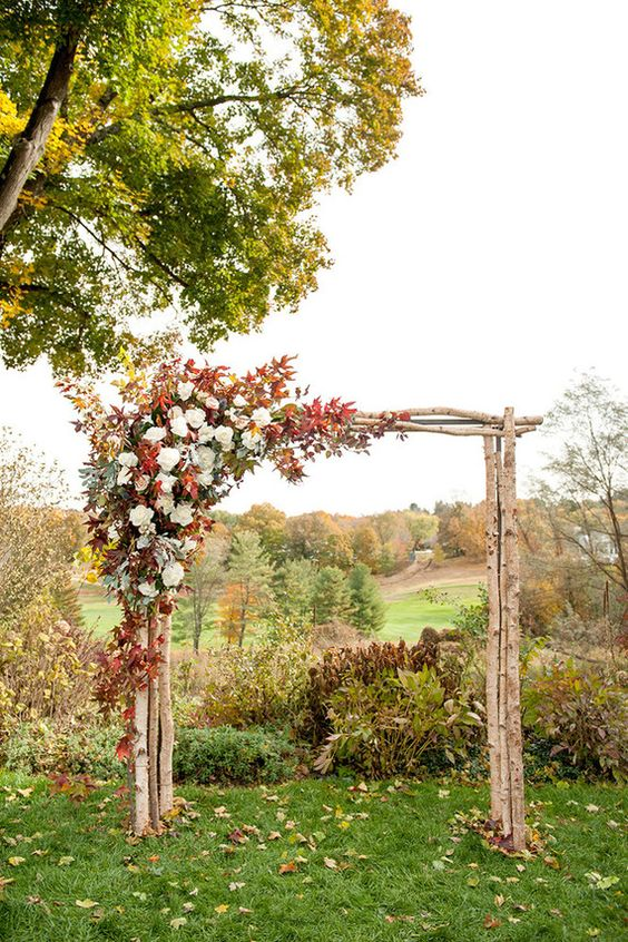 wooden arch with a corner decorated with fall leaves and white flowers
