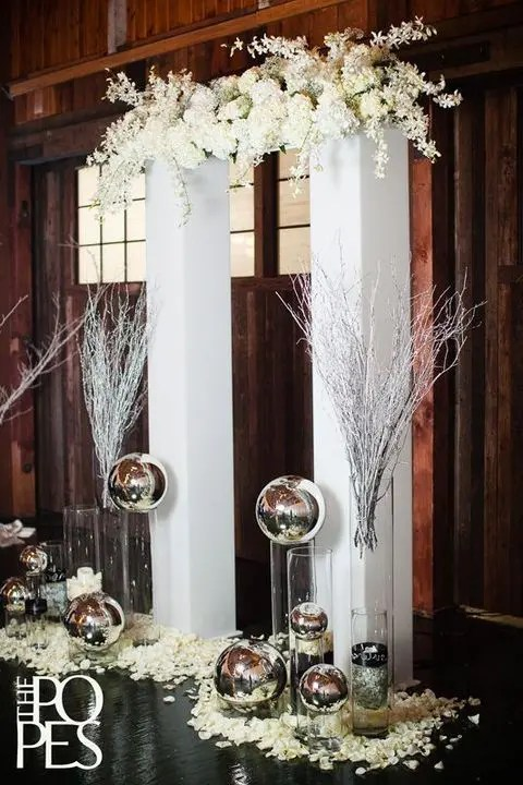 modern indoor arch with white flowers and metal spheres