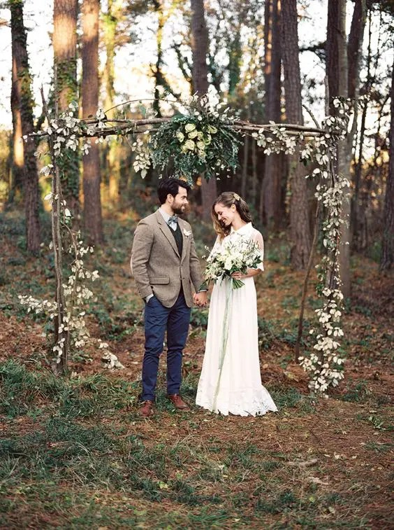 outdoor woodland boho wedding arch decorated with greenery and blooms