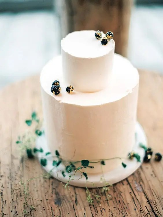 simple frosted cake decorated with berries and greenery
