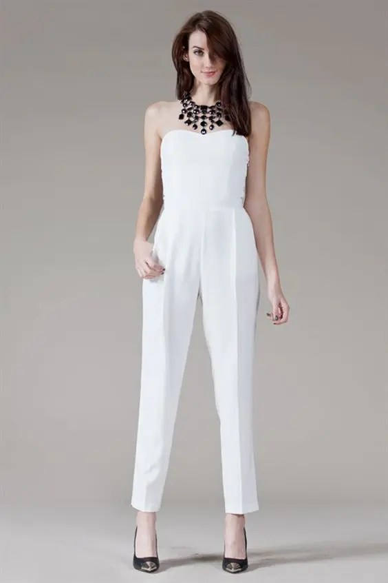 strapless white pantsuit with black heels and a statement necklace