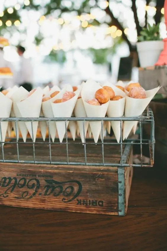 display donuts in paper cones and in wire stands for a rustic wedding