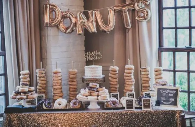 glam donut snack bar with a sequin tablecloth and balloon letters banner